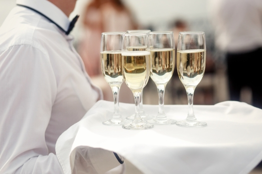 Waiter in white carries tray with champagne flutes